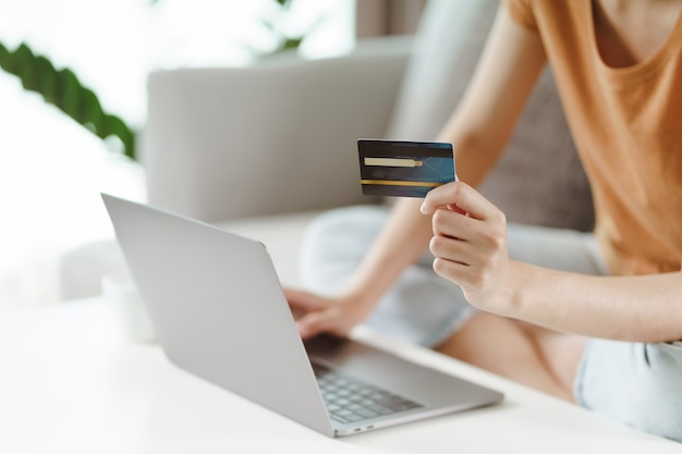 Młoda kobieta posiadania karty kredytowej i przy użyciu komputera przenośnego. zakupy online, bankowość internetowa, e-commerce, wydawanie pieniędzy, praca z koncepcji domu
