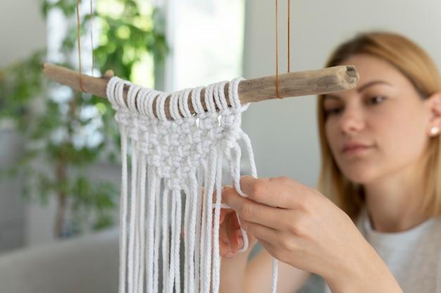 Młoda kobieta posługująca się techniką makramy