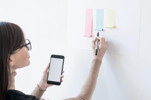 Młoda kobieta pośrednika ze smartfonem i zakreślaczem patrząc na papierowy wykres na tablicy podczas analizy