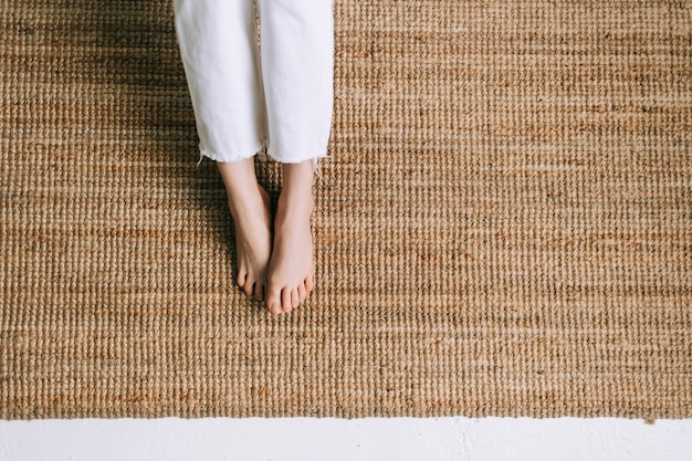 Młoda kobieta postawiła stopy na dywanie z juty wykonanym z naturalnych materiałów