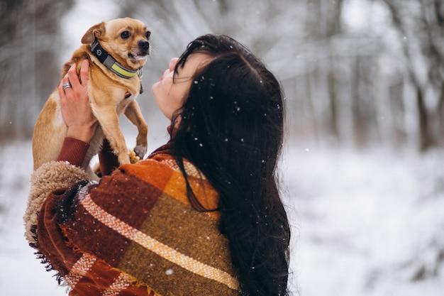 Młoda kobieta poza parkiem z jej małym psem przy zimą