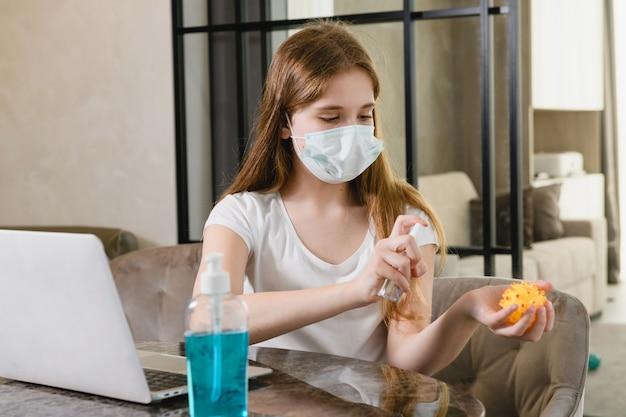 Młoda kobieta pozostaje w domu podczas światowej kwarantanny epidemicznej, nosi maskę ochronną, używa środków antyseptycznych do laptopa, zabawki dla psa i rąk
