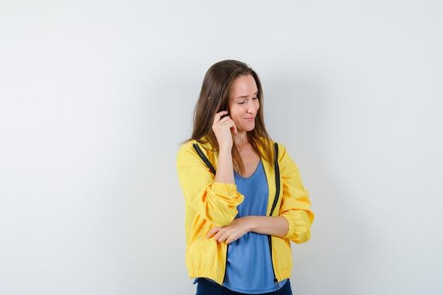 Młoda kobieta pozowanie myśląc w koszulce, kurtce i patrząc optymistycznie. przedni widok.