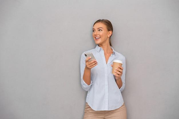 Młoda kobieta pozowanie na białym tle nad szarym tle ściany za pomocą telefonu komórkowego picia kawy.