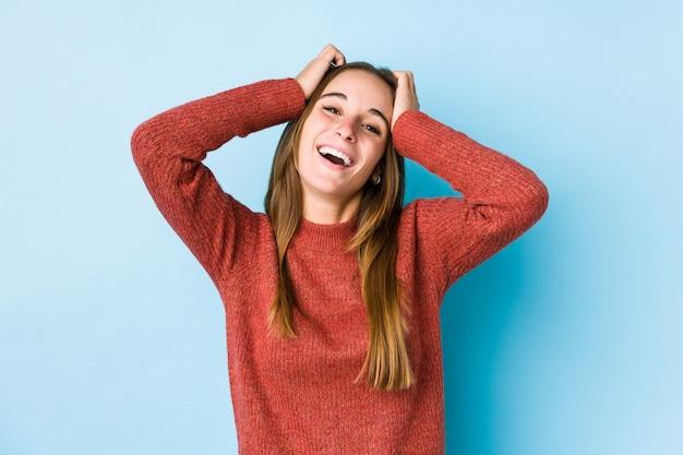 Młoda kobieta pozowanie śmieje się z radością trzymając ręce na głowie. koncepcja szczęścia.