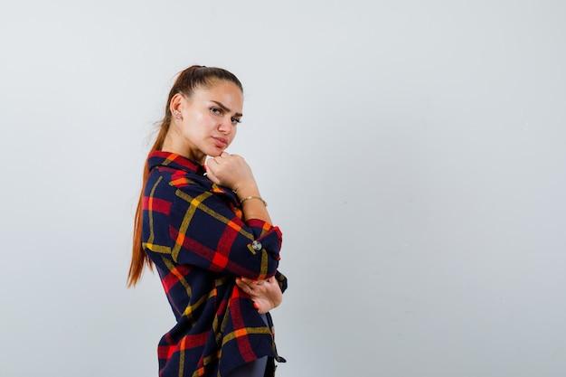 Młoda kobieta pozowanie, stojąc w crop top, kraciaste koszule i patrząc pewnie. przedni widok.