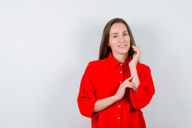 Młoda kobieta pozowanie stojąc w czerwonej bluzce i patrząc delikatny, widok z przodu.