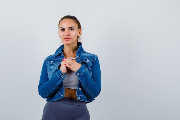 Młoda kobieta pozowanie stojąc w górę, kurtka, spodnie i uroczo patrząc. przedni widok.