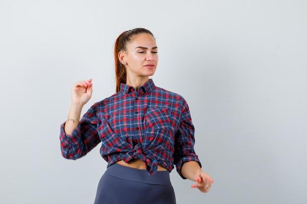 Młoda kobieta pozowanie stojąc w kraciastej koszuli, spodniach i patrząc pewnie, widok z przodu.