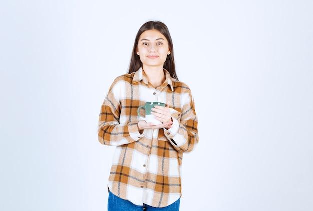 Młoda kobieta pozowanie z filiżanką kawy na białej ścianie.