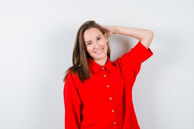 Młoda kobieta pozowanie z ręką na głowie w czerwonej bluzce i patrząc jowialny, widok z przodu.