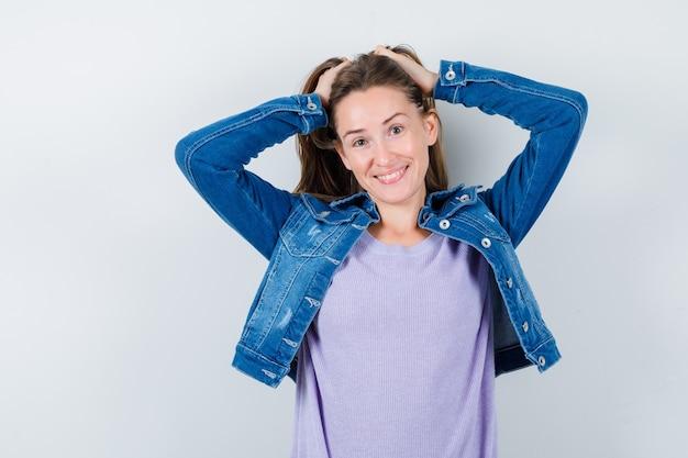 Młoda kobieta pozowanie z rękami na głowie w koszulce, kurtce i patrząc radosny. przedni widok.