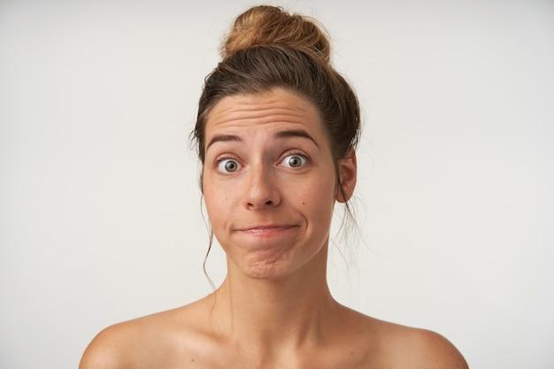 Młoda kobieta pozująca na biało z oszołomioną twarzą, z fryzurą w kok i bez makijażu, marszczone czoło i wydymane usta
