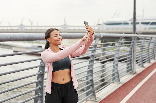 Młoda kobieta pozuje do kamery i robi selfie na telefonie komórkowym podczas treningu sportowego na świeżym powietrzu