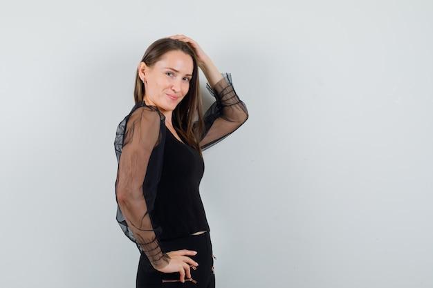 Młoda kobieta pozuje do kamery, uśmiechając się w czarnej bluzce i wyglądając uroczo