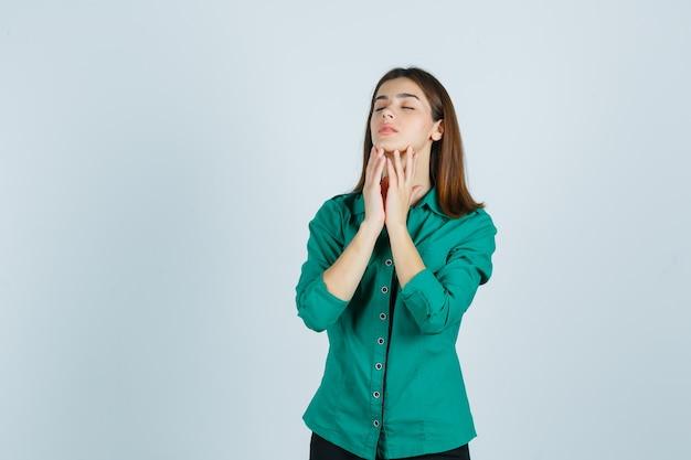 Młoda kobieta pozuje dotykając skóry na brodzie w zielonej koszuli i patrząc wdzięcznie, widok z przodu.