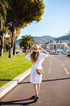 Młoda kobieta pozuje i nosi modną elegancką kobiecą sukienkę i słomiane dodatki