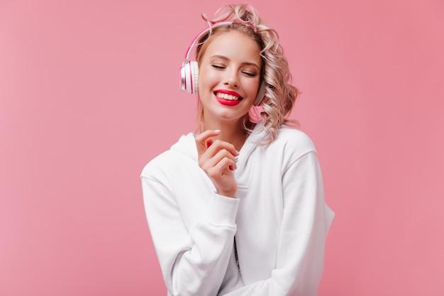 Młoda kobieta pozuje i słucha muzyki przez jej różowe słuchawki