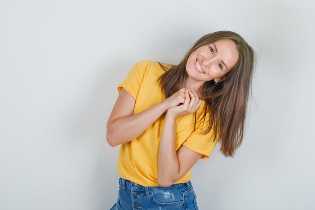 Młoda kobieta pozuje jak prosi o przysługę w żółtej koszulce, szortach i wygląda wesoło