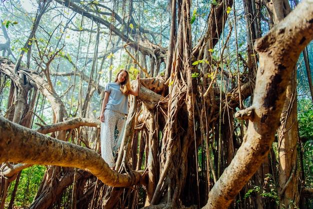 Młoda kobieta pozuje na banyan drzewie