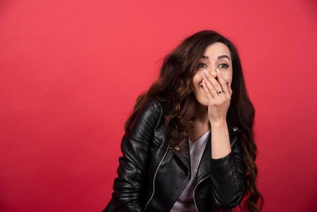 Młoda kobieta pozuje na czerwonym tle. zdjęcie wysokiej jakości