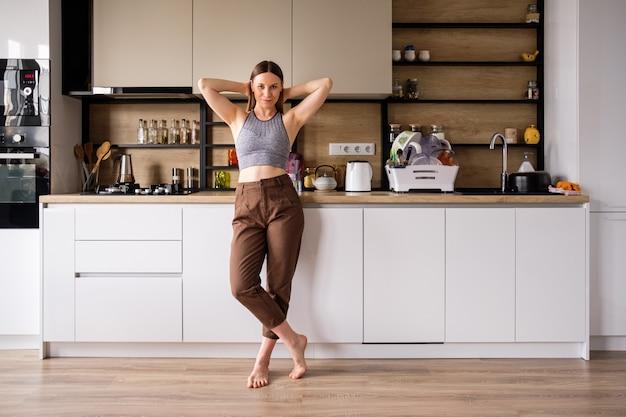 Młoda kobieta pozuje na nowożytnej kuchni