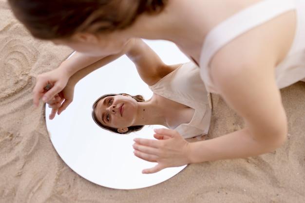 Młoda kobieta pozuje na plaży z okrągłym lustrem