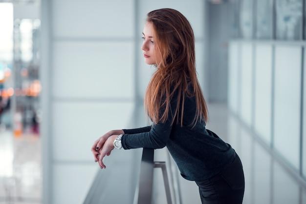 Młoda kobieta pozuje na przeszklonym balkonie.