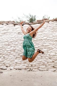 Młoda kobieta pozuje na ściana z cegieł. na zewnątrz styl życia.