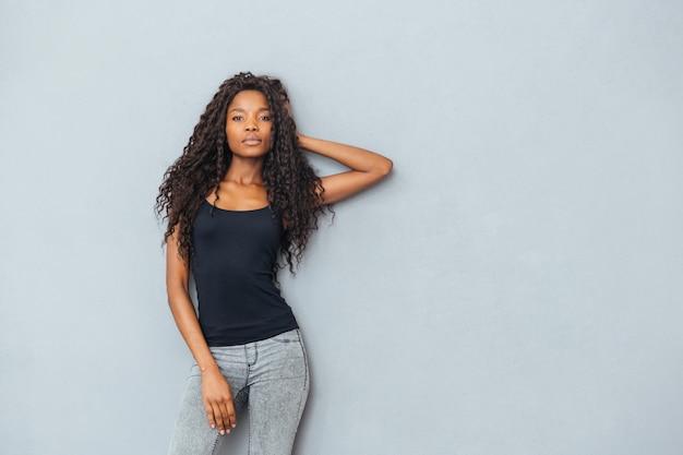 Młoda kobieta pozuje na szarej ścianie