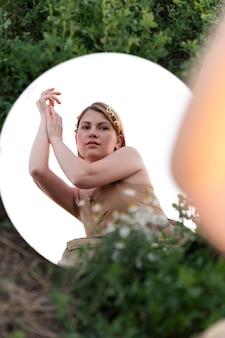 Młoda kobieta pozuje na zewnątrz w polu za pomocą okrągłego lustra