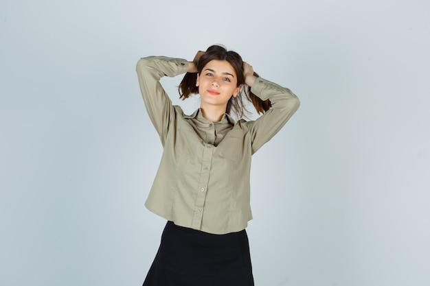 Młoda kobieta pozuje podczas układania włosów w koszuli, spódnicy i wygląda wdzięcznie