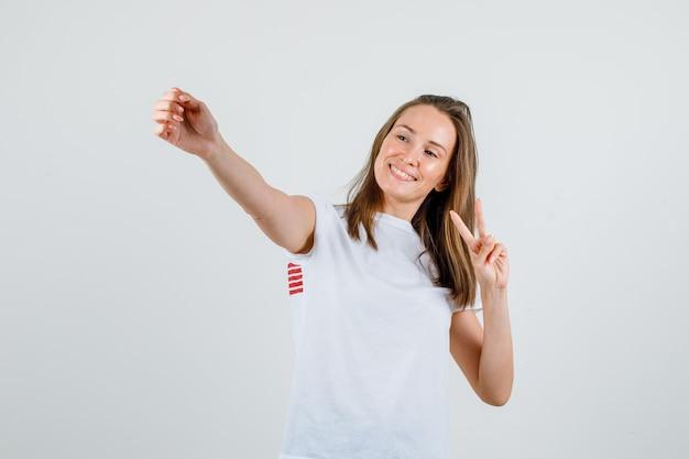 Młoda kobieta pozuje pokazując znak zwycięstwa w białej koszulce i patrząc szczęśliwy. przedni widok.