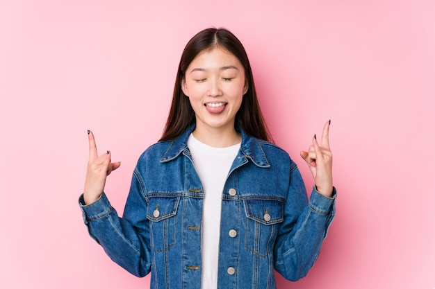 Młoda kobieta pozuje pokazywać rockowego gest z palcami