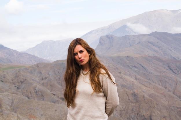 Młoda kobieta pozuje przed góra krajobrazem