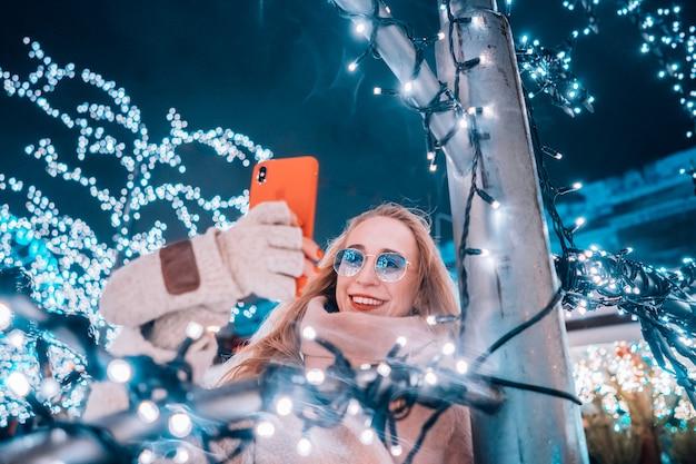 Młoda kobieta pozuje przy ulicą z iluminującymi drzewami