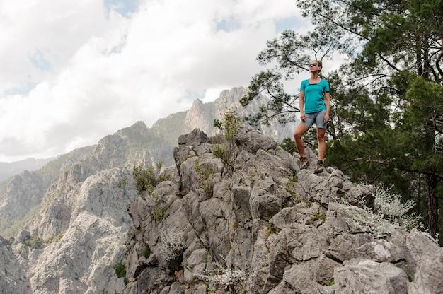 Młoda kobieta pozuje przy wierzchołkiem góra