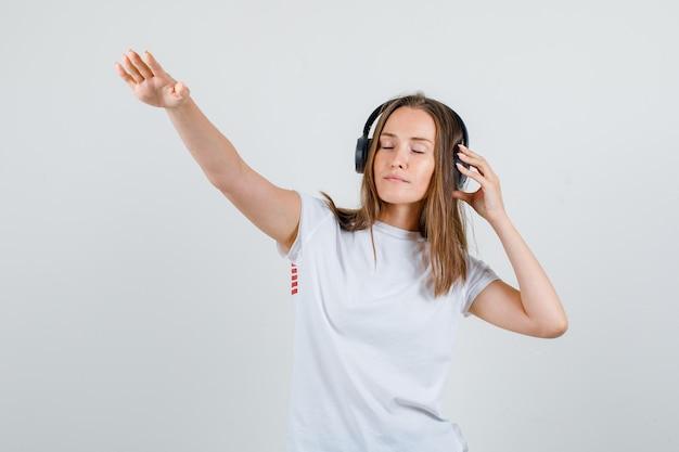 Młoda kobieta pozuje trzymając słuchawki w białej koszulce i patrząc zrelaksowany