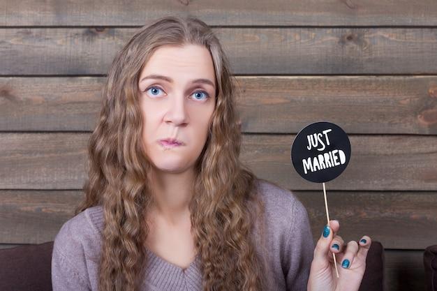 Młoda kobieta pozuje twarz i pokazuje zabawną ikonę na patyku z napisem właśnie żonaty