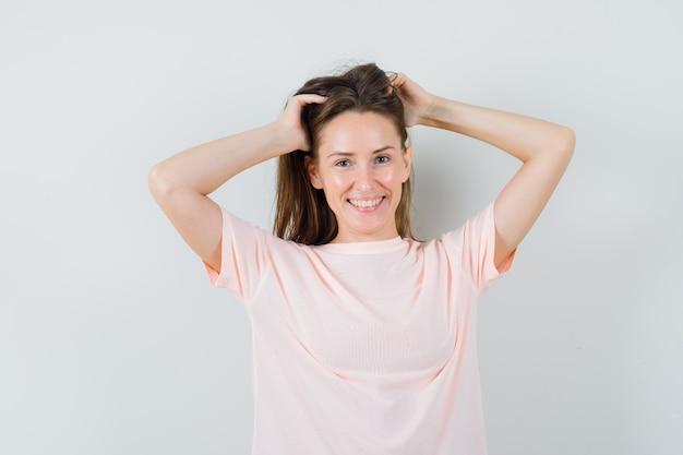 Młoda kobieta pozuje układając włosy w różową koszulkę i pięknie wyglądając, widok z przodu.