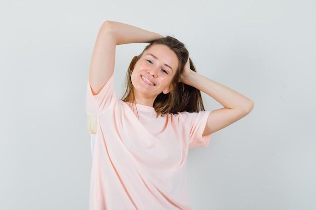 Młoda kobieta pozuje układając włosy w różowej koszulce i wygląda oszałamiająco.