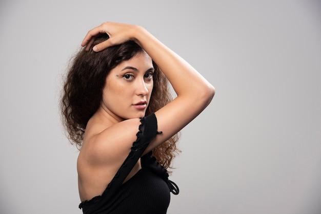 Młoda kobieta pozuje w czarnej bluzce z kręconymi włosami. wysokiej jakości zdjęcie