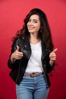 Młoda kobieta pozuje w czarnych okularach na czerwonym tle. zdjęcie wysokiej jakości