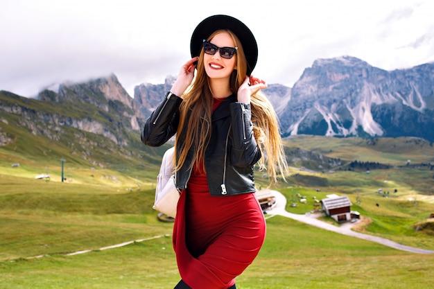 Młoda kobieta pozuje w górach alp, ubrana w sukienkę, skórzaną kurtkę, okulary przeciwsłoneczne i plecak