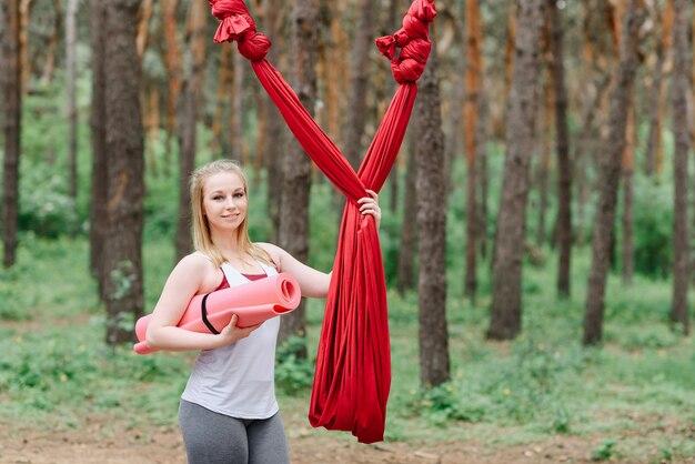 Młoda kobieta pozuje w parku, stojąc przy hamaku z matą do jogi.