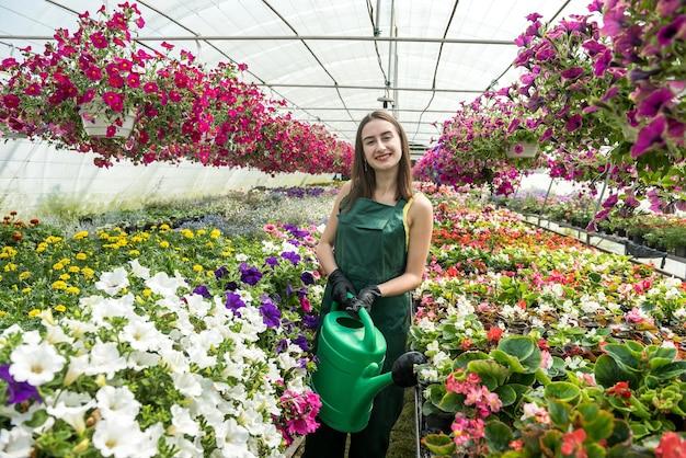 Młoda kobieta pozuje w szklarni kwiatowy