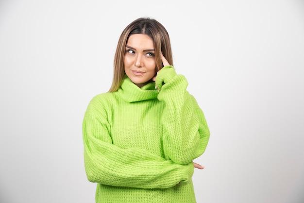 Młoda kobieta pozuje w zielonej koszulce na białej ścianie.