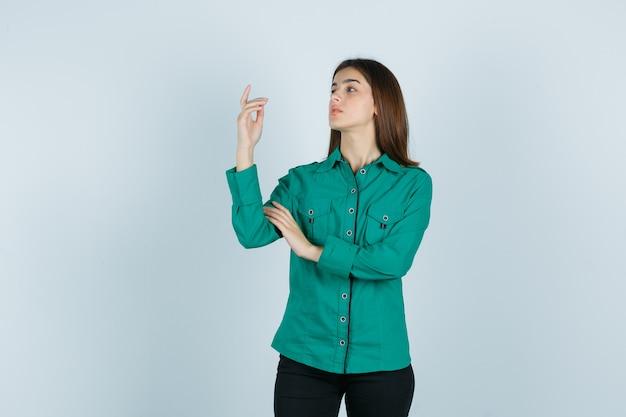 Młoda kobieta pozuje, wskazując w zielonej koszuli, spodniach i wygląda wspaniale. przedni widok.