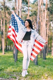 Młoda kobieta pozuje z flaga amerykańską w parku