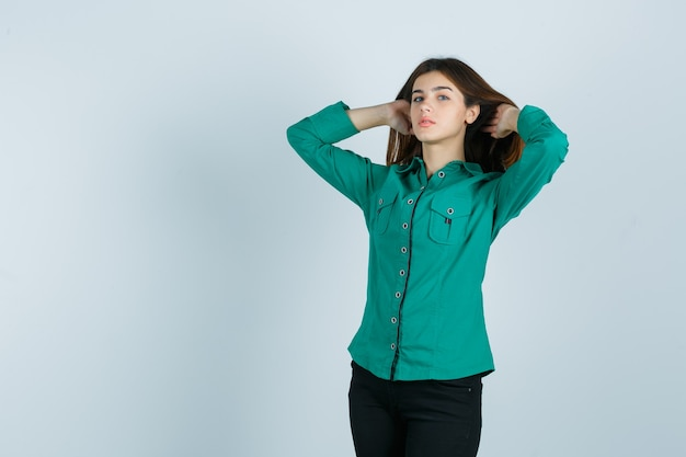 Młoda kobieta pozuje z kasztanowymi włosami w zielonej koszuli, spodniach i wygląda pociągająco. przedni widok.